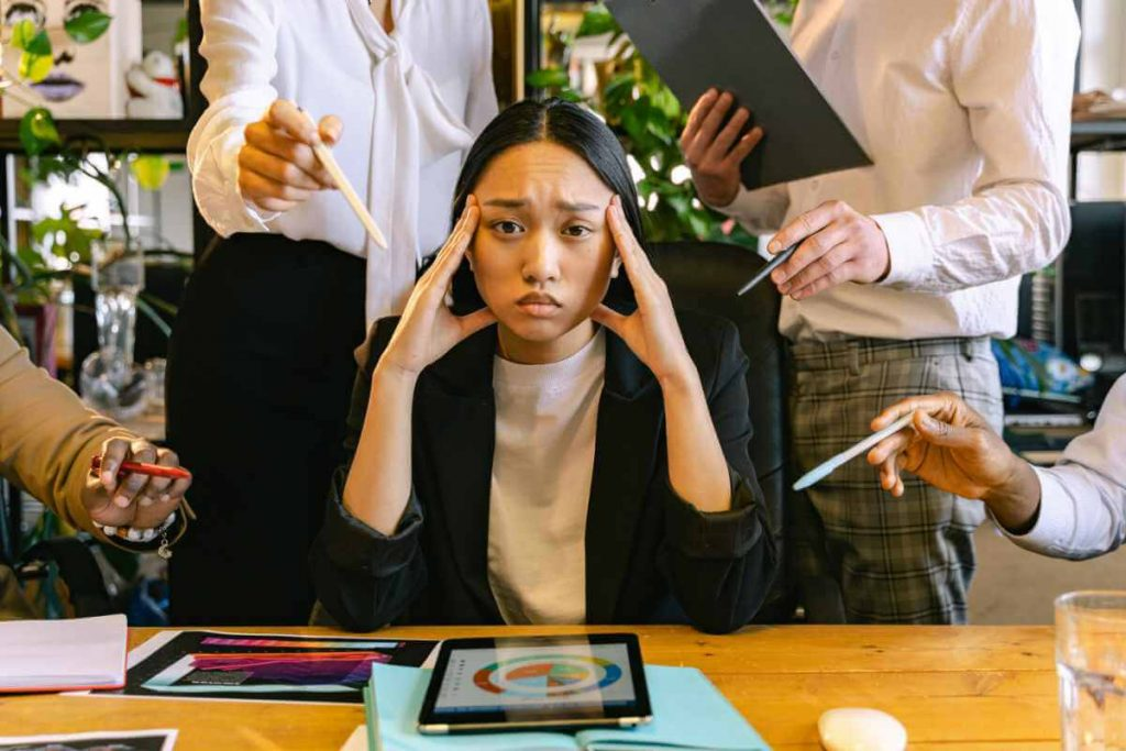 Image - stressed person surrounded by people
